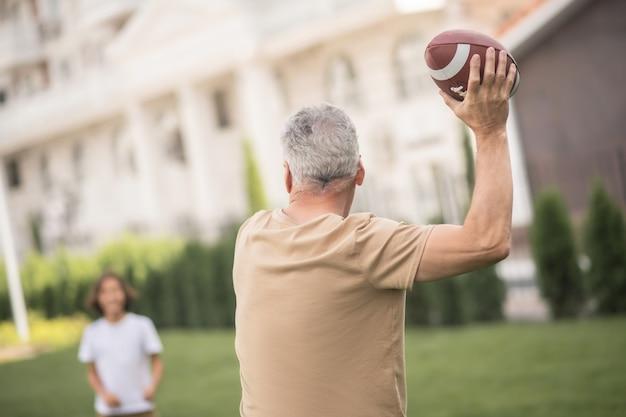 Dobra gra. tata rzuca piłką podczas zabawy z synem