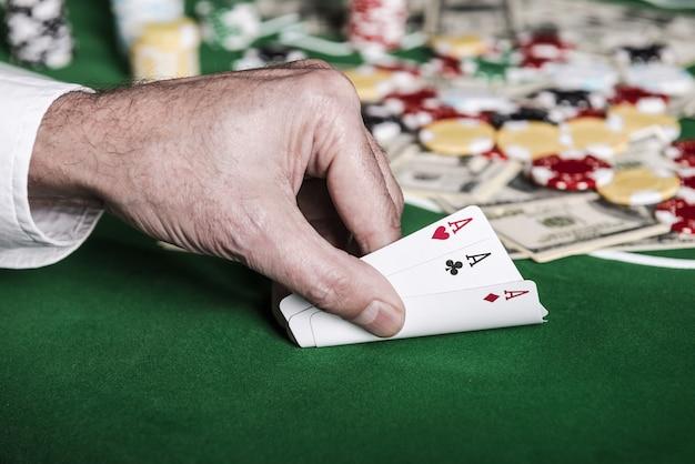 Dobra kombinacja. zbliżenie męskiej ręki pokazującej swoje karty na stole pokerowym z żetonami i pieniędzmi leżącymi w tle