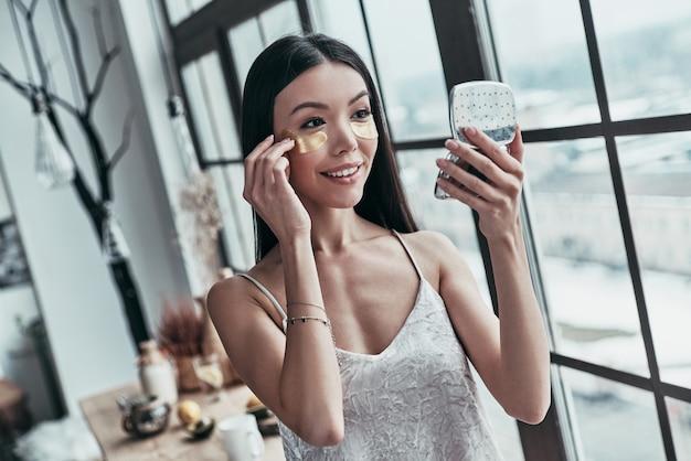 Dobra opieka. atrakcyjna młoda kobieta używająca opasek na oczy i uśmiechająca się podczas spędzania czasu w domu