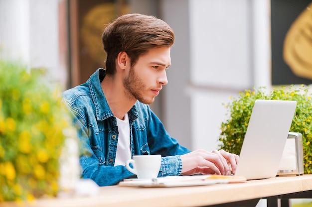 Dobra pogoda na spędzenie czasu w kawiarni. skoncentrowany młody człowiek pracujący na laptopie
