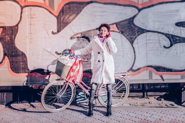 Dobra pogoda. stylowa osoba płci żeńskiej, demonstrując swój płaszcz, patrząc prosto w kamerę