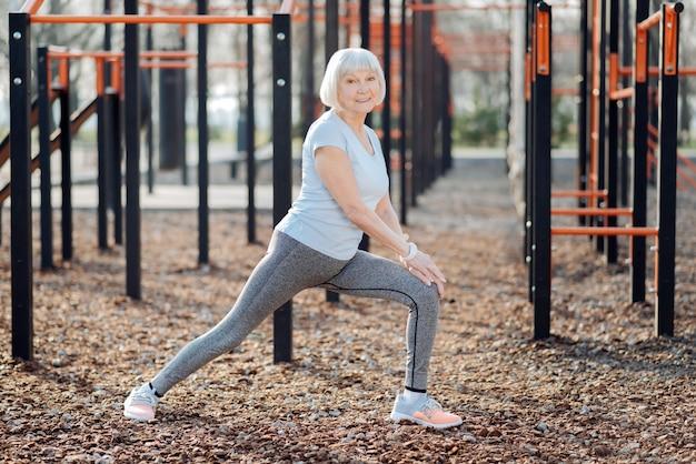 Dobra pogoda. zainspirowana szczupła kobieta uśmiechając się i ćwicząc na świeżym powietrzu