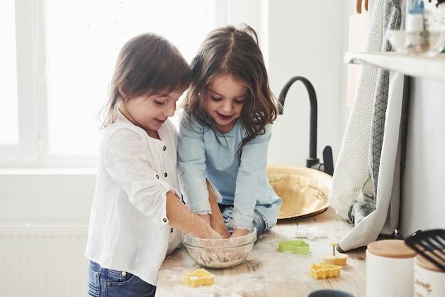 Dobra praca zespołowa. przyjaciele z przedszkola uczą się gotować z mąki w białej kuchni.