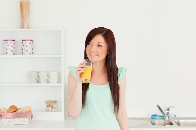 Dobra przyglądająca miedzianowłosa kobieta cieszy się szkło sok pomarańczowy w kuchni