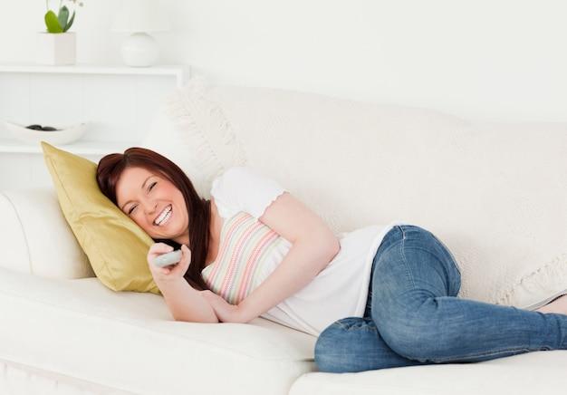 Dobra przyglądająca miedzianowłosa kobieta ogląda tv podczas gdy kłamający na kanapie