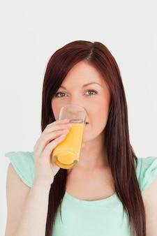 Dobra przyglądająca miedzianowłosa kobieta pije szkło sok pomarańczowy w kuchni