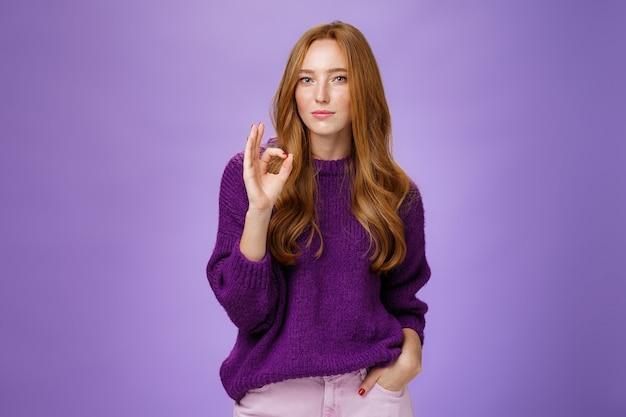 Dobra robota, fajnie. portret zachwyconej stylowej i pewnej siebie rudowłosej kobiety w fioletowym swetrze, pokazującej ok gest w odpowiedzi na doskonałą pracę, dumnej z koleżanki nad fioletową ścianą.
