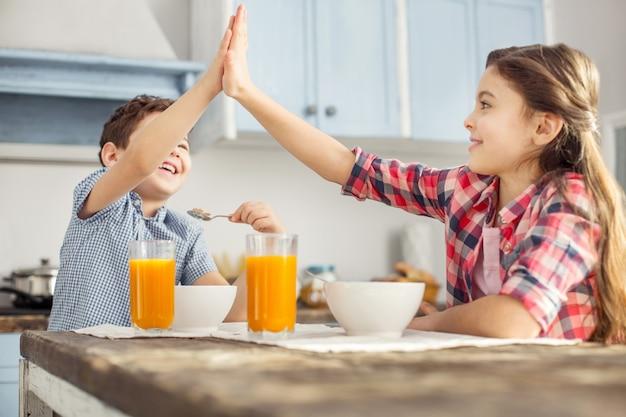 Dobra robota. piękna zainspirowana ciemnowłosa dziewczynka uśmiecha się i patrzy na swojego brata, gdy jedzą śniadanie i przybijają mu piątkę