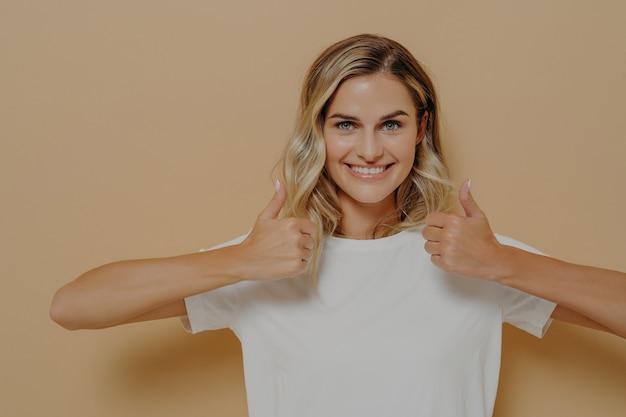 Dobra robota. pozytywna młoda blondynka ubrana w białą koszulkę casual, codzienną odzież, która robi kciuk w górę obiema rękami i demonstruje poprawę, pozując na beżowym tle