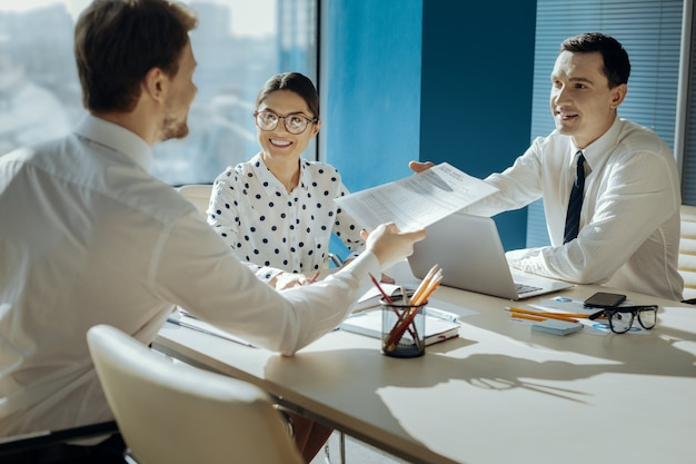 Dobra robota. przystojny młody analityk przekazuje wyniki badań swojemu szefowi podczas spotkania w swoim gabinecie