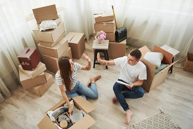 Dobra robota, teraz jest nasza. wesoła młoda para w swoim nowym mieszkaniu. koncepcja ruchu.