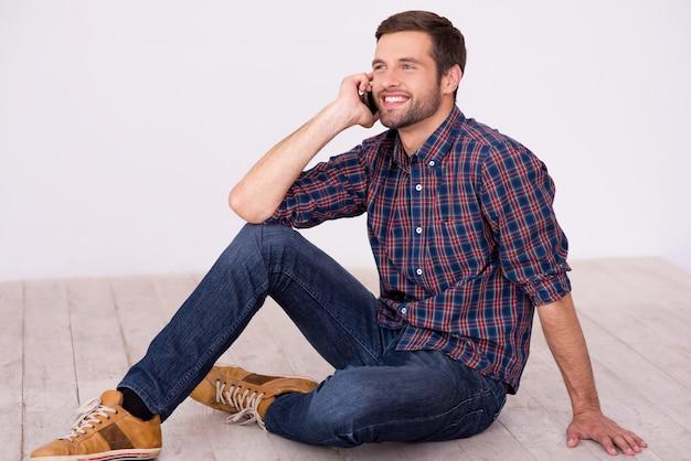Dobra rozmowa z przyjacielem. przystojny młody mężczyzna rozmawia przez telefon komórkowy i uśmiecha się do kamery siedząc na drewnianej podłodze