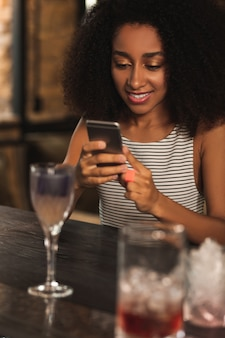 Dobra rozrywka. piękne kręcone kobiety siedzące przy barze i wysyłające sms-y do swojej najlepszej przyjaciółki, popijając koktajl w barze