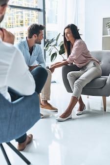 Dobra sesja. młode małżeństwo rozmawia i uśmiecha się siedząc na sesji terapeutycznej