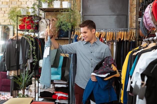 Dobra sprzedaż. wesoły przystojny młody człowiek patrząc na szorty i ciesząc się niesamowitą sprzedażą w sklepie z ubraniami