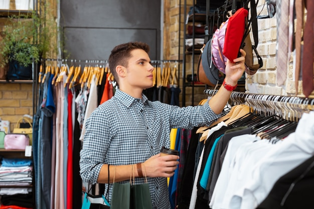 Dobra torba. spokojny przystojny młody mężczyzna dotyka czerwonej nerki, stojąc przy filiżance kawy w sklepie z ubraniami