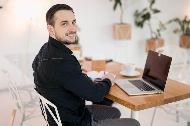 Dobra umowa z klientem. młody szczęśliwy freelancer mężczyzna w czarnych ubraniach dorywczo patrząc na kamery, używając swojego laptopa i pamiętnika, patrząc na kamery i uśmiechając się. udana koncepcja pracy zdalnej.