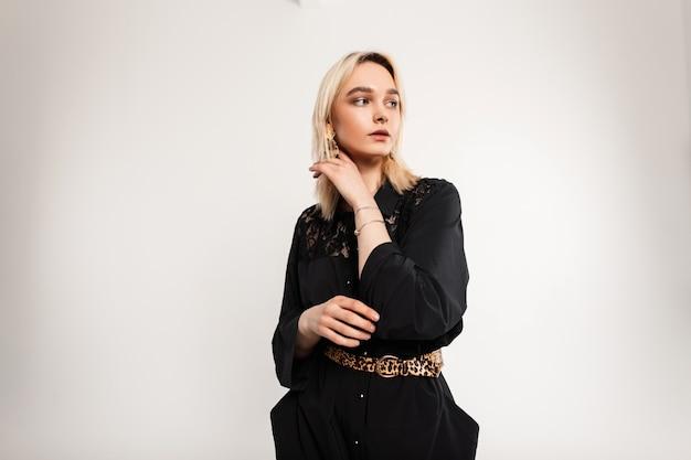 Dobra urocza młoda kobieta o blond włosach z seksownymi ustami w czarnej modnej sukience z paskiem w panterkę pozowanie w pobliżu białej ściany vintage