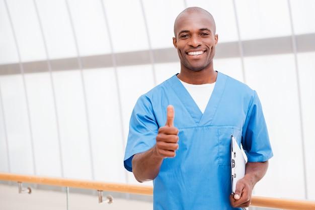Dobra wiadomość dla ciebie! szczęśliwy młody afrykański lekarz w niebieskim mundurze trzymający schowek i pokazujący kciuk w górę