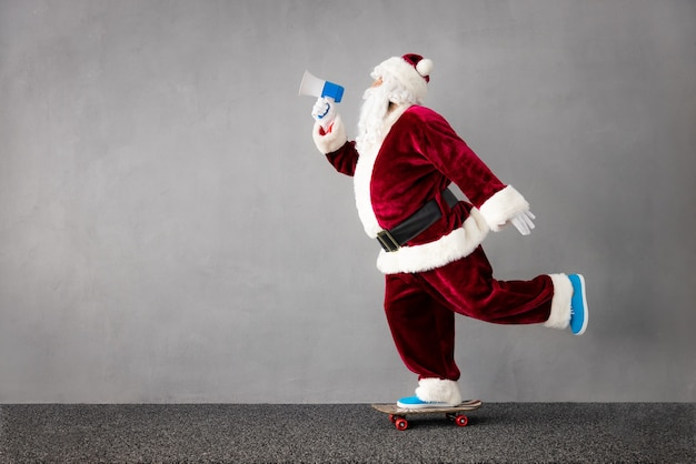 Dobra wiadomość święty mikołaj jedzie na deskorolce portret starszego mężczyzny w stroju świątecznym