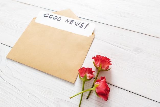 Dobra wiadomość w brązowej kopercie z czerwonymi kwiatami na białym drewnianym