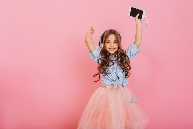 Dobra zabawa, wyrażanie prawdziwych pozytywnych emocji radosnej, niesamowitej młodej dziewczyny słuchającej muzyki w słuchawkach na różowym tle. szczęśliwe dzieciństwo słodkie dziecko. miejsce na tekst
