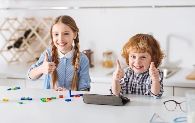 Dobra zabawa z korzyściami. piękne, mądre i energiczne dzieci, które wyrażają swoją pozytywną wysokość, trzymając kciuki do góry i wyglądając na całkiem radosne