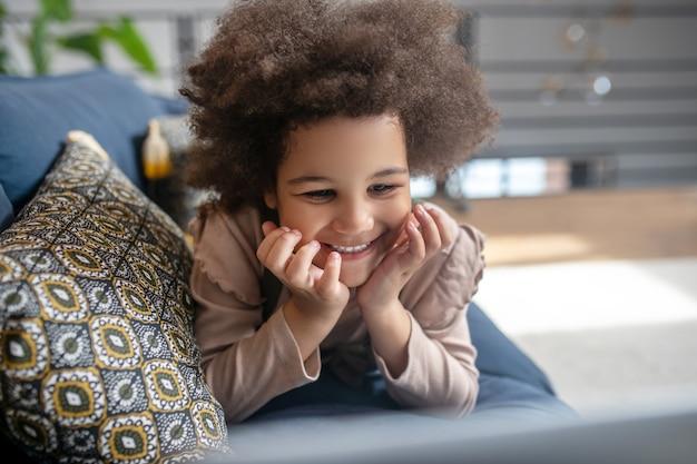 Dobre chwile. śliczna radosna mała ciemnoskóra dziewczynka leżąca na kanapie z poduszkami na brzuchu trzymająca się za ręce w pobliżu uśmiechniętej twarzy