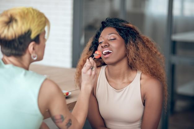 Dobre chwile. zrelaksowana młoda śliczna amerykańska kobieta z otwartymi ustami i dziewczyną z wyciągniętym pomidorem na widelcu