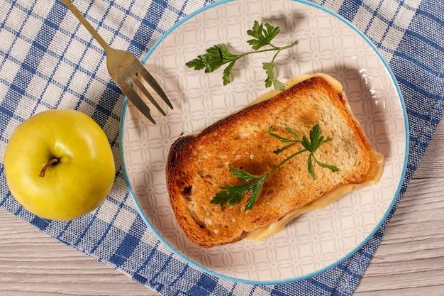 Dobre i smaczne jedzenie i napoje na śniadanie. tosty z masłem i serem na talerzu z widelcem i jabłkiem na serwetce kuchennej. widok z góry