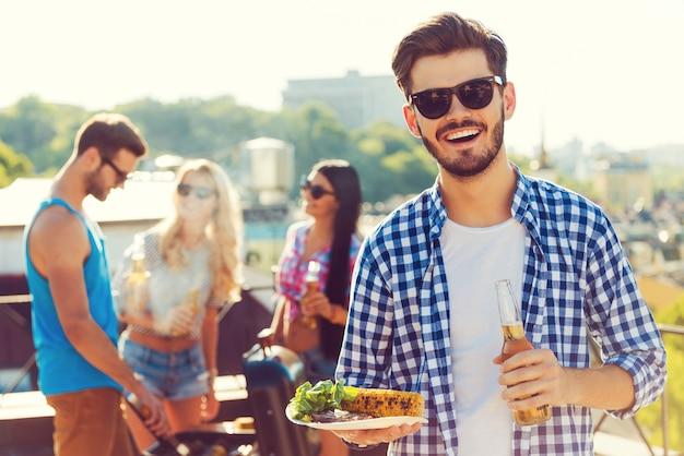 Dobre jedzenie z najlepszymi przyjaciółmi. uśmiechnięty młody mężczyzna trzymający butelkę z piwem i talerz z jedzeniem, podczas gdy trzy osoby grillują w tle