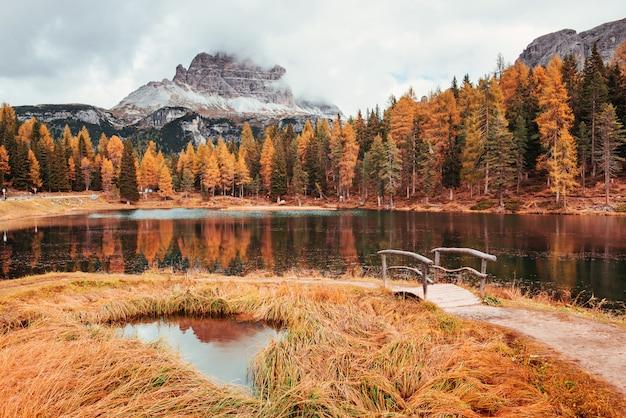 Dobre miejsce na odpoczynek. niesamowity widok na majestatyczne góry z lasami przed nimi w jesienny dzień. kałuża, która wychodzi z jeziora z małym mostkiem