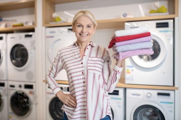 Dobre mycie. uśmiechnięta blondynka gospodarstwa stos ręczników i dobre samopoczucie