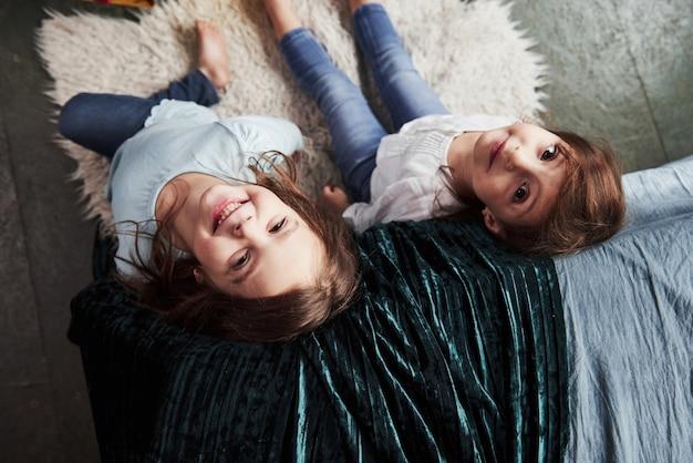 Dobre samopoczucie i uśmiech. widok z góry na dwoje wesołych dzieci siedzących