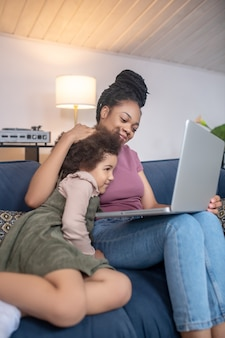 Dobre samopoczucie. kochająca młoda dorosła ciemnoskóra mama przytulająca małą kędzierzawą córkę patrzącą razem na laptopa w domu na kanapie