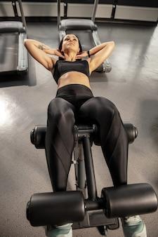 Dobre samopoczucie. młoda muskularna kobieta kaukaski ćwiczenia w siłowni ze sprzętem. wysportowana modelka robi ćwiczenia abs, trenuje górną część ciała, brzuch. wellness, zdrowy styl życia, kulturystyka.
