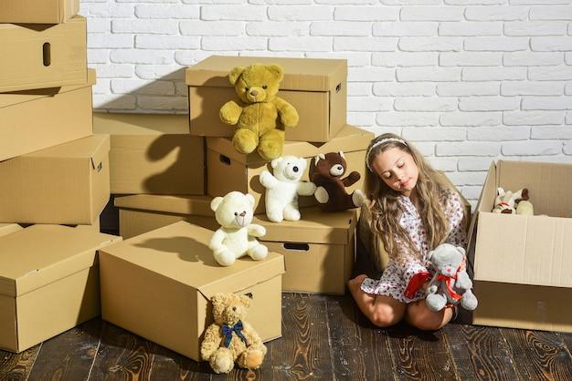 Dobre samopoczucie w domu. potrzebuje tylko zabawek. dom jest tam, gdzie są moje zabawki. wprowadzamy się. słodki dom. dziecko dziewczynka relaks po rozpakowaniu pudełek. świadczenie usług. tylko niezbędne rzeczy. koncepcja pokoju zabaw.