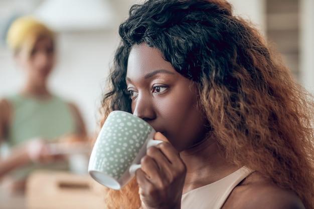 Dobre samopoczucie. zamknij się ładna twarz zamyślonej młodej amerykańskiej kobiety z długimi kręconymi włosami picia kawy w domu i dziewczyną w tyle