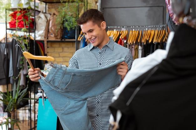 Dobre spodenki. wesoły młody człowiek uśmiecha się i czuje się szczęśliwy, trzymając piękne szorty w modnym sklepie