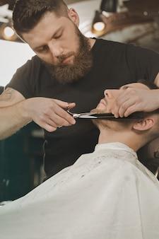 Dobre stare nożyczki. pionowo strzał fryzjer męski przycina brodę jego klient używa nożyce
