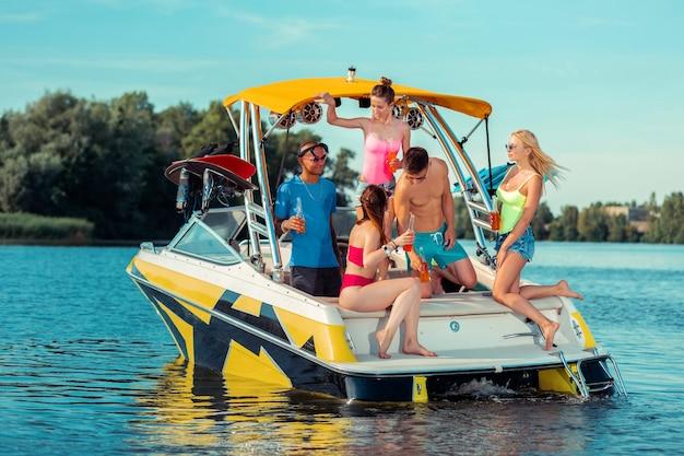 Dobre towarzystwo. uśmiechnięci młodzi ludzie z butelkami napojów bezalkoholowych na łodzi wycieczkowej, patrzący na siebie podczas rozmowy