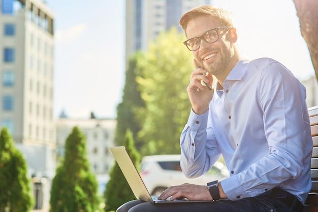 Dobre wieści młody szczęśliwy biznesmen rozmawia przez telefon i uśmiecha się siedząc na ławce