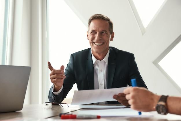Dobre wieści. przystojny i wesoły dojrzały mężczyzna w wizytowym gestem i uśmiechnięty siedząc w biurze. ludzie biznesu. spotkanie biznesowe