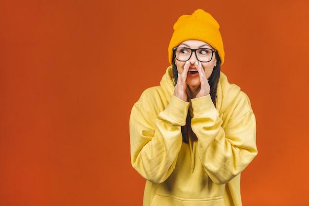 Dobre wieści! rozochocona szczęśliwa ładna dziewczyna mówi sekret na pomarańczowym tle.