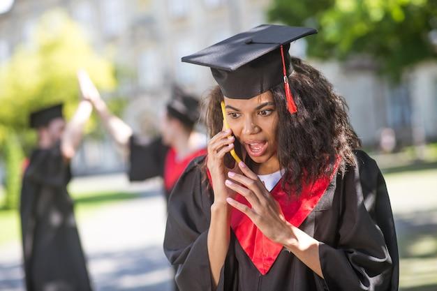 Dobre wieści. śliczna dziewczyna w akademickiej sukni rozmawia przez telefon