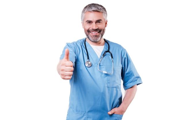 Dobre wieści. szczęśliwy dojrzały chirurg w niebieskim mundurze, patrząc na kamerę i uśmiechając się stojąc na białym tle
