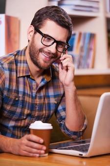 Dobre wieści! szczęśliwy młody człowiek rozmawia przez telefon komórkowy i patrząc na swojego laptopa, pijąc kawę i siedząc przy biurku z półką na książki w tle