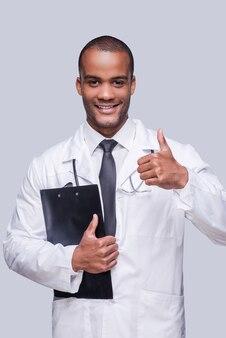 Dobre wieści. wesoły afrykański lekarz pokazujący kciuk w górę i uśmiechnięty