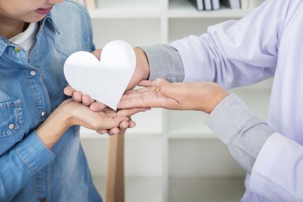 Dobroczynności, opieki zdrowotnej, darowizny i pojęcia medycyny - ręka mężczyzny lekarz dając serce pacjenta