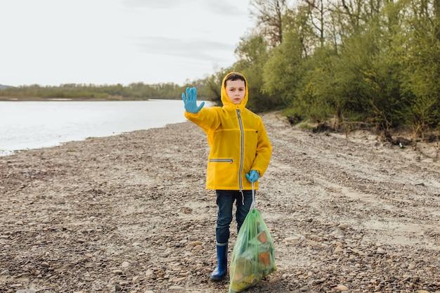 Dobry chłopak-wolontariusz wyrzuci czarne worki na śmieci do kosza. chłopiec ma śmierdzące śmieci.